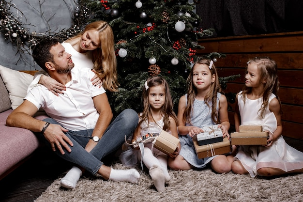 Famiglia carina felice con tre bambini che si scambiano i regali sotto l'albero di natale sul tappeto.