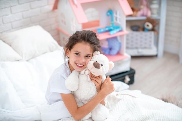 Felice ragazza carina seduta sul letto nella sua camera per bambini e abbracci orsacchiotto.