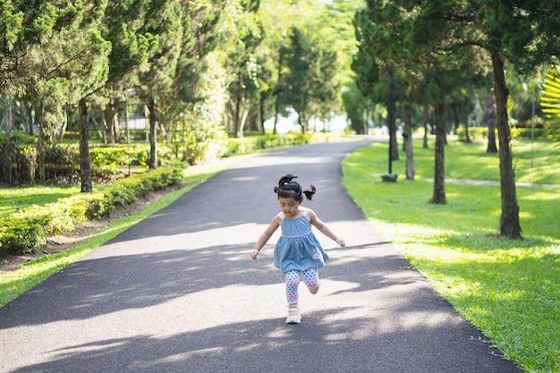 Ragazza carina felice che sorride e corre in giardino