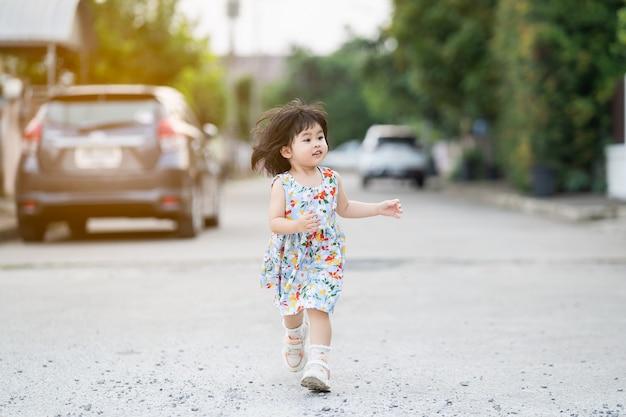 Ragazza carina felice che sorride e corre sulla strada