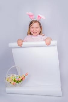 Felice ragazza carina con orecchie da coniglio. sfondo cartolina d'auguri di pasqua. con le uova di pasqua e la merce nel cestino del fiore di primavera