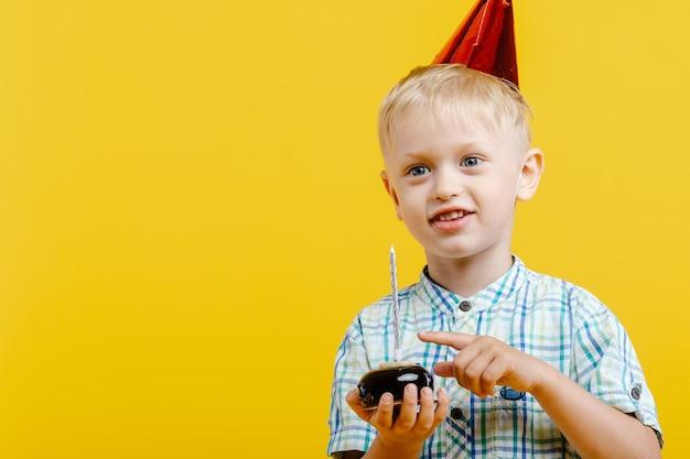 Ragazzino sveglio felice nel cappello di compleanno e con la torta sul giallo.
