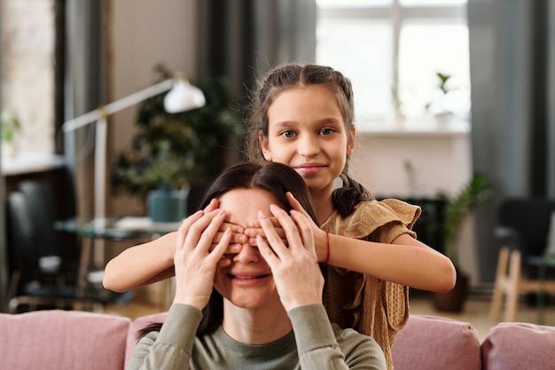 Bambina sveglia felice che copre gli occhi della sua mamma sorridente con le mani