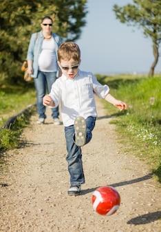 Felice figlio carino che gioca con il pallone da calcio nel parco e sua madre incinta che guarda sullo sfondo