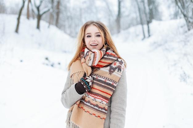 Giovane donna alla moda carina felice in un cappotto grigio vintage con sciarpa calda di lana alla moda in guanti sta camminando in un bosco innevato. la ragazza allegra allegra gode della natura invernale.