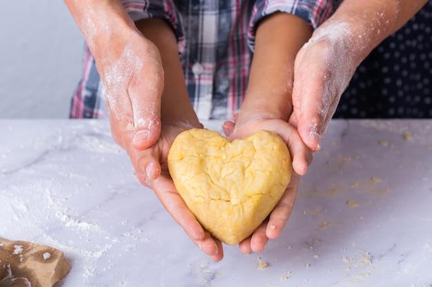 Felice ragazzo carino che tiene in mano un pezzo di pasta fatta in casa a forma di cuore. tempo in famiglia nell'accogliente cucina. attività autunnale a casa. aiuto e formazione compiti per bambini