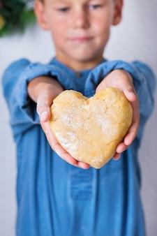Felice ragazzo carino che tiene in mano un pezzo di pasta fatta in casa a forma di cuore. tempo in famiglia nell'accogliente cucina. attività invernale a casa. aiuto e formazione compiti per bambini