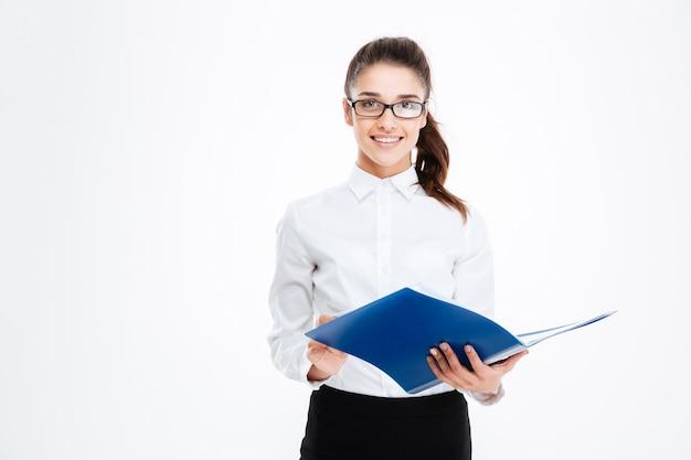 Felice carino giovane donna d'affari con gli occhiali in piedi e tenendo la cartella sul muro bianco