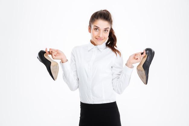 Felice carino giovane donna d'affari che tiene scarpe con tacchi alti su muro bianco