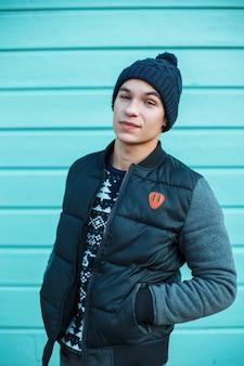 Felice carino giovane uomo in un maglione lavorato a maglia con un ornamento di natale in un berretto vintage in una giacca invernale alla moda stare sulla strada vicino al muro di legno blu. ragazzo gioioso moderno ed elegante.