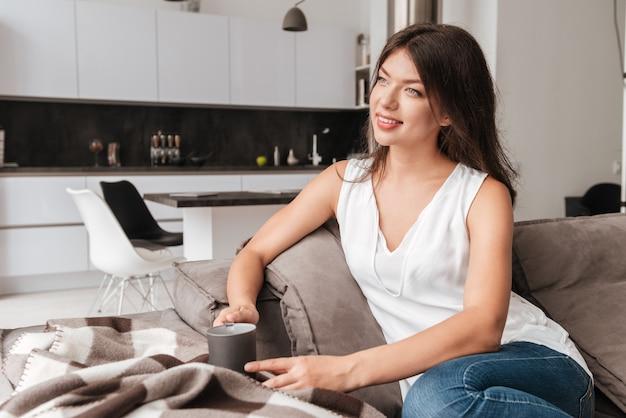 Felice carino giovane donna che beve il caffè sul divano di casa
