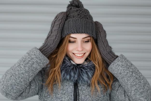 Felice carina giovane donna in un cappello grigio lavorato a maglia in un elegante cappotto con pelliccia in guanti vintage lavorati a maglia con un bel sorriso vicino al muro bianco di metallo. la ragazza allegra gode del fine settimana.