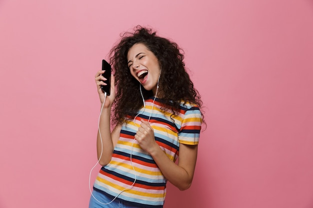 Felice carino giovane donna in posa isolata sul rosa utilizzando la musica d'ascolto del telefono cellulare.