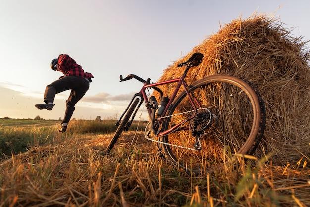 Felice ciclista che salta in un campo con un pagliaio e una bicicletta in piedi nelle vicinanze al tramonto. allenamento ciclistico attivo.