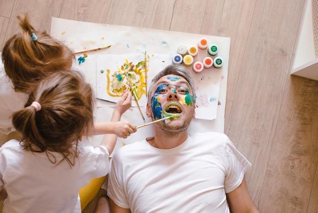 Papà felice è sdraiato sul pavimento, i bambini si dipingono il viso con gli acquerelli. festa del papà. papà felice