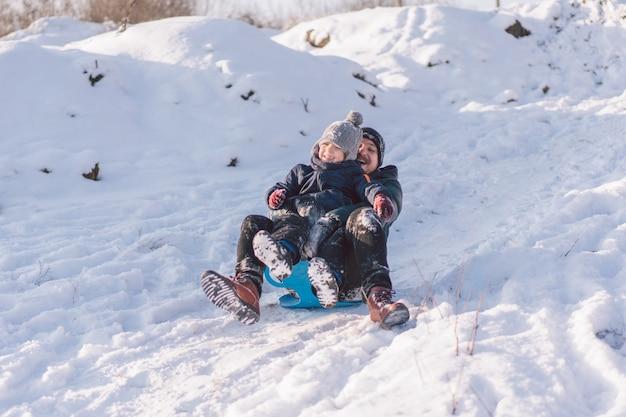 Papà felice e ragazzino che giocano con la slitta da neve