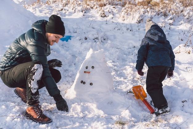 Papà felice e ragazzino che giocano con la neve