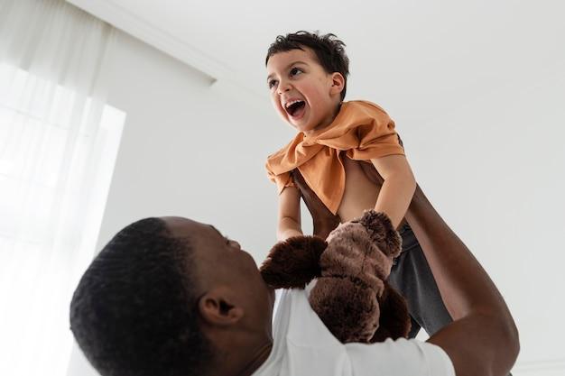 Papà felice che aumenta suo figlio mentre gioca