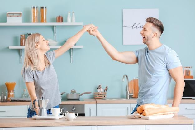 Felice giovane coppia che balla in cucina