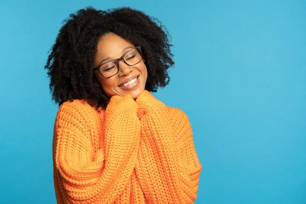 Felice donna millenaria dalla pelle scura con i capelli ricci indossare maglione lavorato a maglia arancione