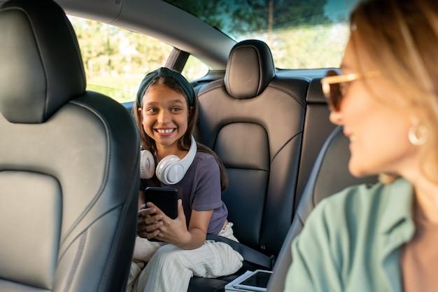 Figlia felice che guarda sua madre durante la chat all'interno dell'auto