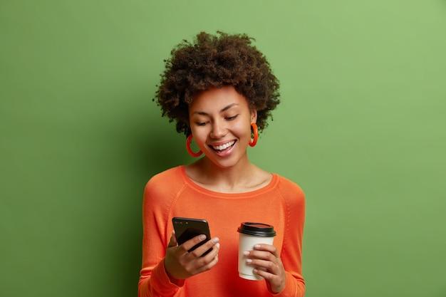 La donna dai capelli ricci felice e felice tiene la tazza di caffè di carta e lo smartphone ha un bel discorso online amichevole indossa il ponticello arancione isolato sopra la parete verde