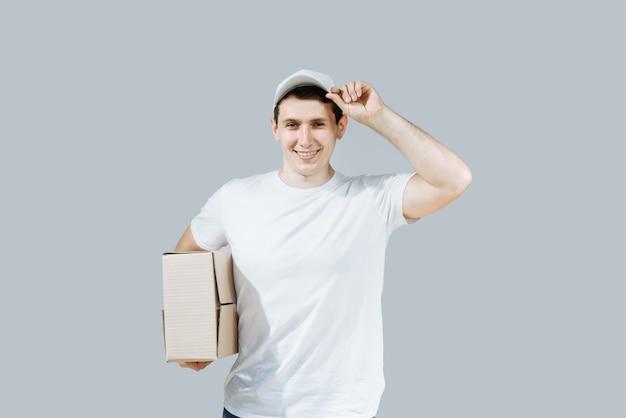 Uomo di consegna felice con una scatola in uniforme.