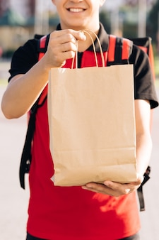 Felice fattorino che tiene in mano un pacchetto di cibo guardando la telecamera e sorridendo in un ritratto ravvicinato