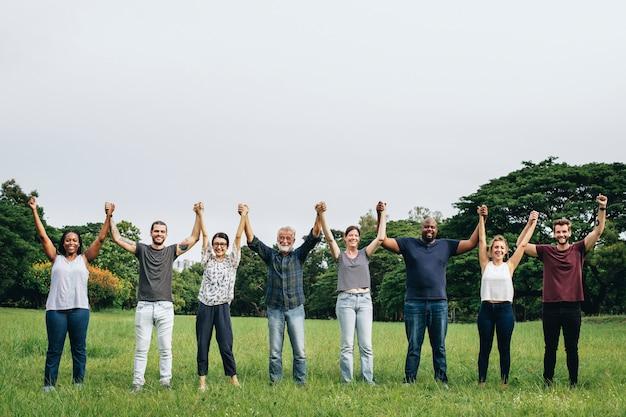 Diversa gente felice che si tiene per mano nel parco