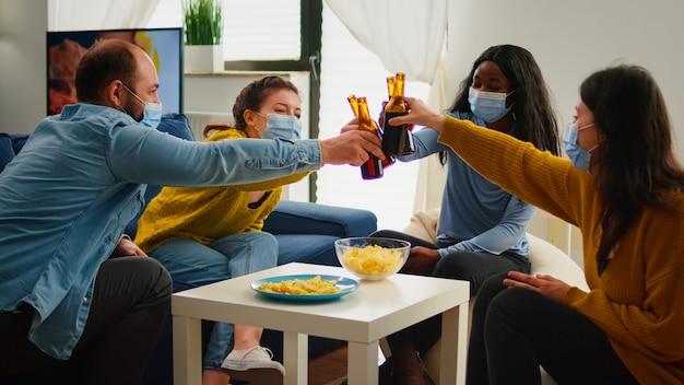 Felici e diversi giovani che si divertono in soggiorno, tintinnando bottiglie di birra che raccontano storie e barzellette durante la pandemia globale. gruppo multietnico di amici che festeggiano con un brindisi nell'epidemia