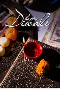 Biglietto di auguri diwali felice che mostra lampada a olio o diya con petardi, mithai, frutta secca, banconote indiane, fiori di calendula e statua della dea laxmi o lakshmi
