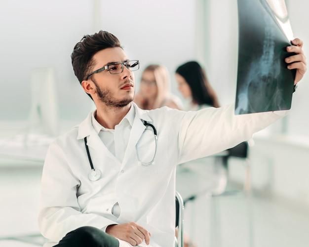 Il radiologo felice del medico esamina i raggi x