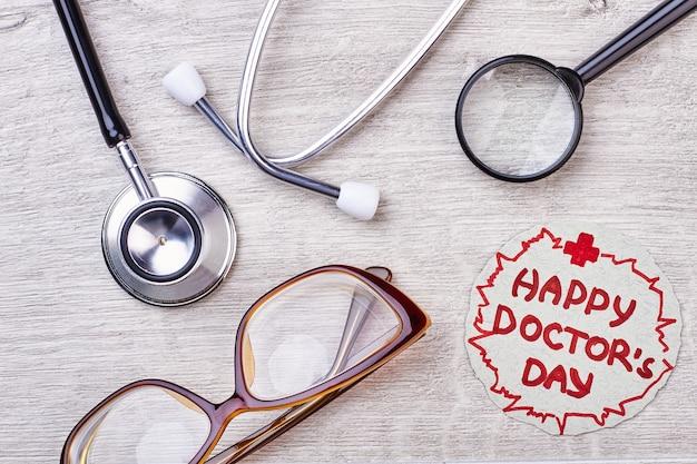 Iscrizione di saluto del giorno del dottore felice. occhiali e stetoscopio su legno.