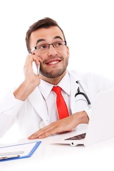 Un dottore felice che parla al telefono in ufficio