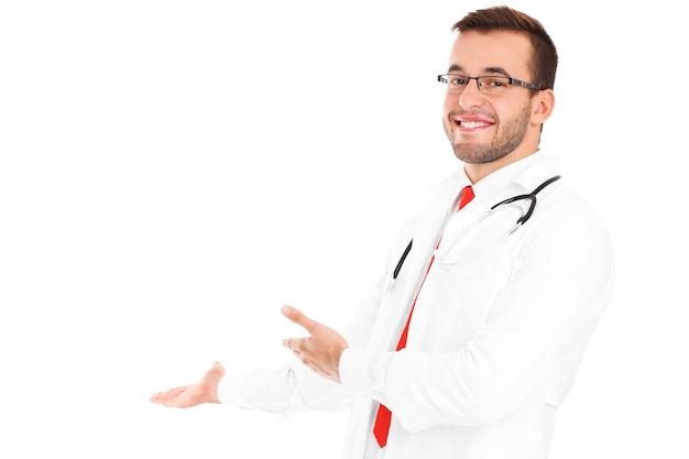 Un medico felice con lo stetoscopio che mostra il tuo prodotto su sfondo bianco