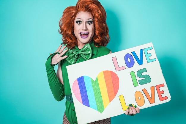 Felice drag queen che tiene il banner dell'orgoglio gay - lgbtq e concept - focus on face