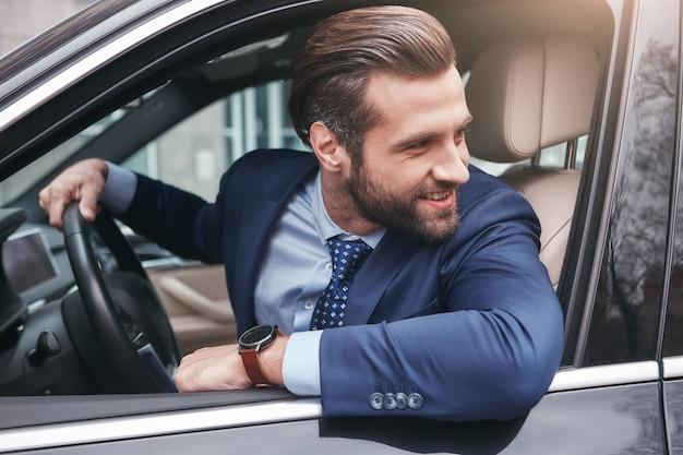 Autista felice felice ed elegante giovane uomo d'affari in abito completo sta guardando attraverso la finestra
