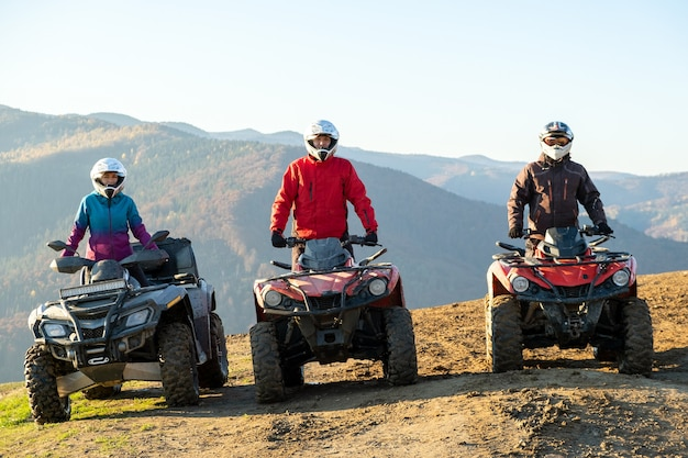 Autisti felici in caschi protettivi che si godono un giro estremo su moto quad atv in montagne autunnali al tramonto.