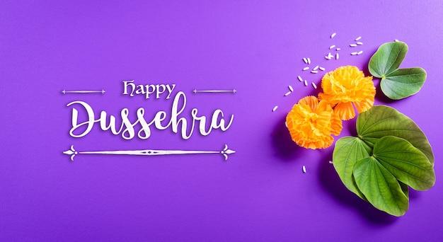 Felice dussehra. fiori gialli, foglia verde e riso su sfondo pastello viola