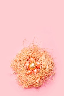 Sfondo di pasqua felice, uova colorate di rosa e d'oro nel nido di fieno su un colore rosa brillante