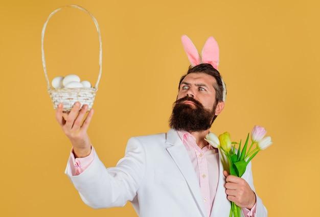 Buona pasqua. maschio barbuto con cesto di uova e bouquet di fiori primaverili. uomo coniglio in orecchie da coniglio.