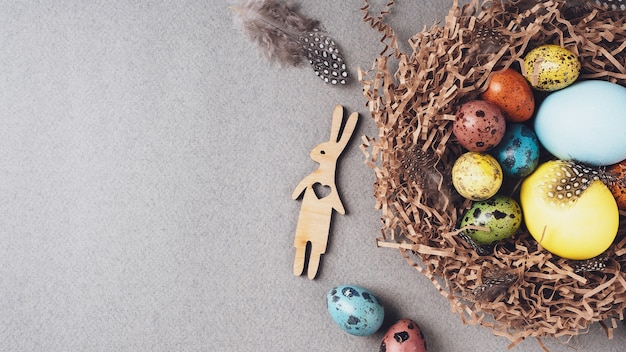 Buona pasqua. sfondo luminoso di pasqua di congratulazioni. vista dall'alto, distesi, copia spazio. uova di pasqua colorate, coniglietto e piume in un nido su uno sfondo grigio, primo piano.