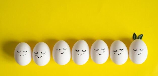 Carta di buona pasqua. uova di pasqua sveglie con una faccia dipinta in foglie di primavera su giallo