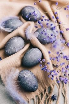 Carta di pasqua felice con uova blu, fiori, piume