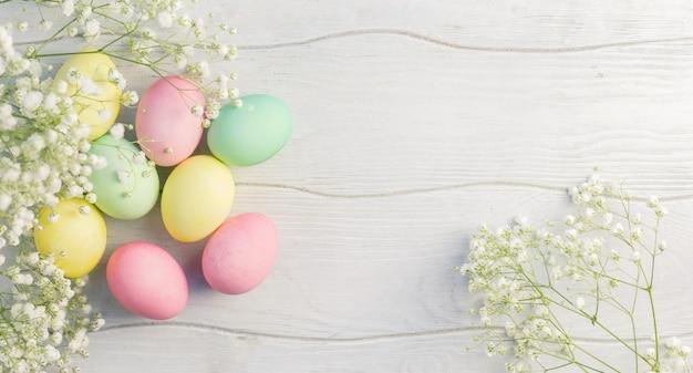 Carta di pasqua felice con uova multicolori e fiori dai toni pastello.