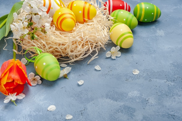 Carta di pasqua felice con uova dipinte e fiori sul tavolo colorato, sfondo vacanza per la tua carta. caccia alle uova, copia dello spazio