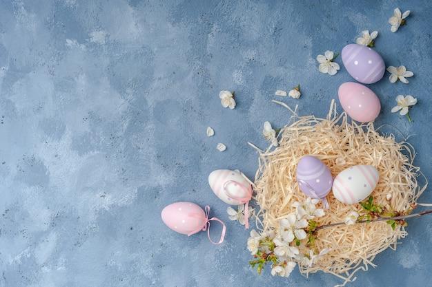 Carta di pasqua felice con uova dipinte e fiori sul tavolo colorato, superficie di vacanza per la tua carta. caccia alle uova, copia dello spazio