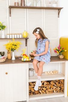 Buona pasqua. il bambino si sta preparando per la pasqua. una ragazza si siede in una cucina decorata e tiene le uova colorate di pasqua.
