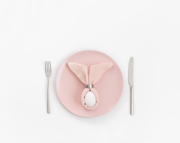 Felice concetto di pasqua. tavola di pasqua con uovo in tovagliolo rosa coniglietto di pasqua su uno sfondo bianco. copia spazio, vista dall'alto, piatto laici.