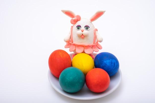 Buona pasqua concetto. uova di pasqua dipinte a mano e un coniglietto di plastilina fatto a mano in una gonna rosa su sfondo bianco, vista dall'alto. fai da te. decorazione divertente.